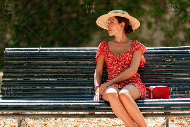 Carefree female in summer dress and straw hat standing near trees in lush garden and looking away while enjoying nature