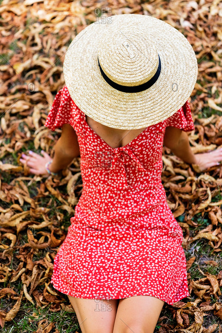 High angle of slim female in light dress and straw hat sitting on dried leaves on meadow in garden and enjoying summer weekend