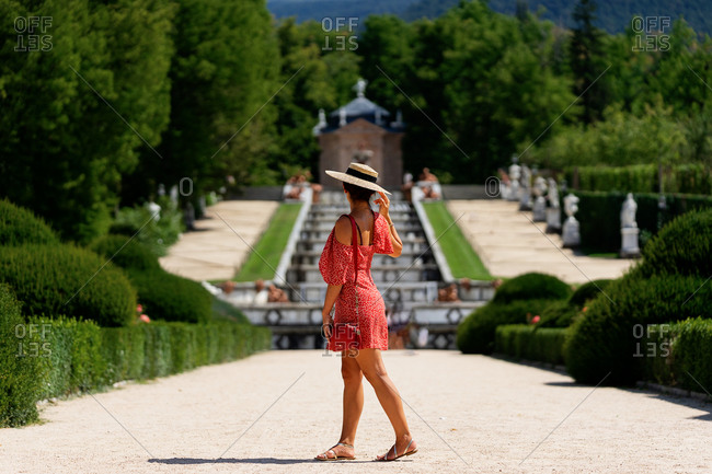 Side view of unrecognizable female tourist in summer dress and straw hat standing in garden on sunny day and enjoying holiday