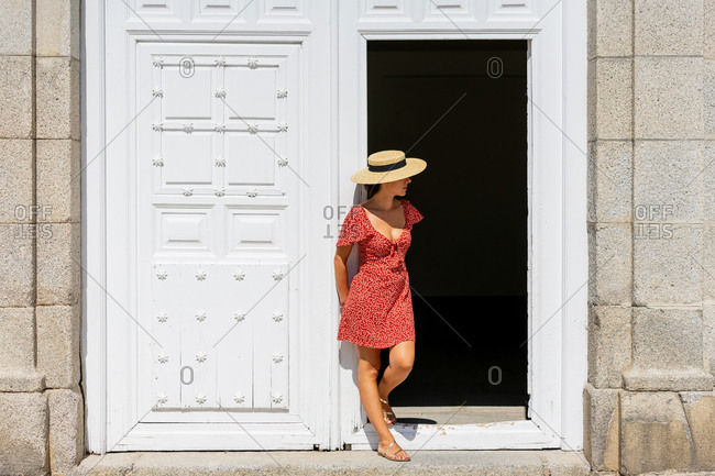 Slim female traveler wearing summer dress and straw hat leaning on wooden door of old building in city during vacation and looking away