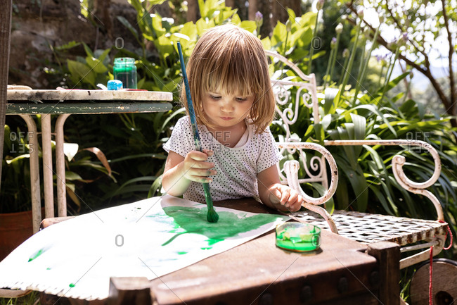 Cute blond girl in white shirt sitting at table in sunny garden and drawing picture with green watercolor