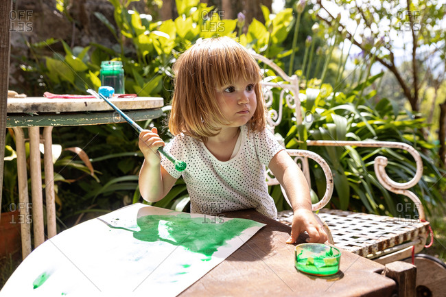 Side view concentrated little girl in casual clothes painting picture with watercolor while spending summer day with family in sunny park