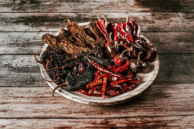 From above of bright various dry chili peppers with wrinkled peel on rustic plate on wooden table