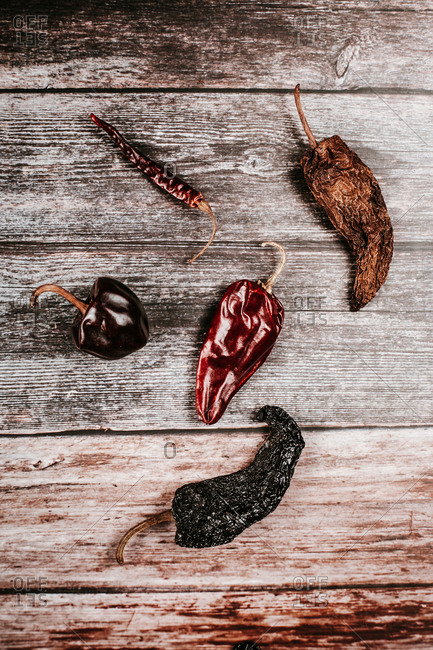 Top view of different dry hot peppers with pedicels and shiny surface on rustic table