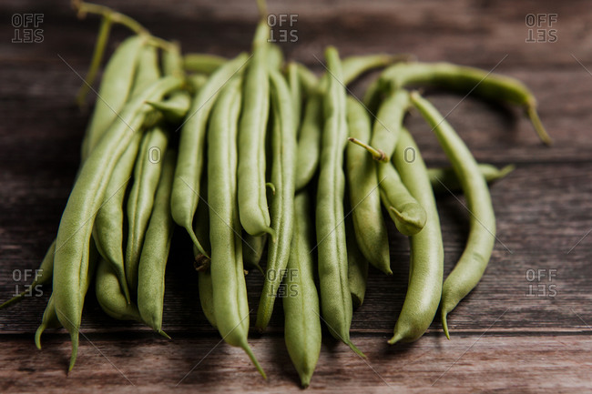 Top view of bundle of fresh green beans on wooden rustic surface