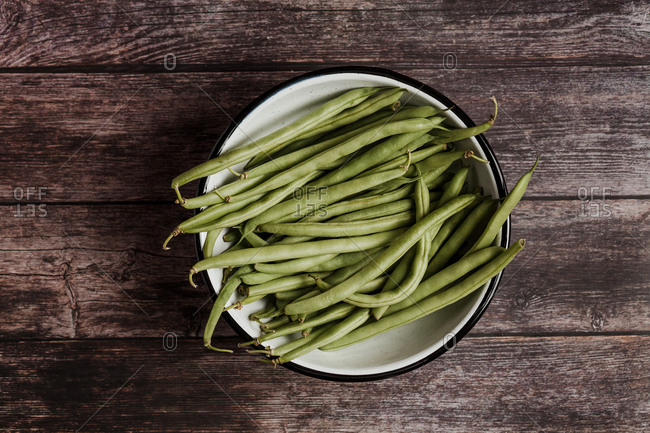 Top view of fresh whole and cut green beans on metal bowl in a wooden table