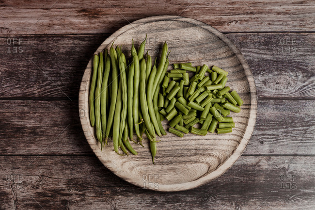 Top view of fresh whole and cut green beans in wooden bowls on table