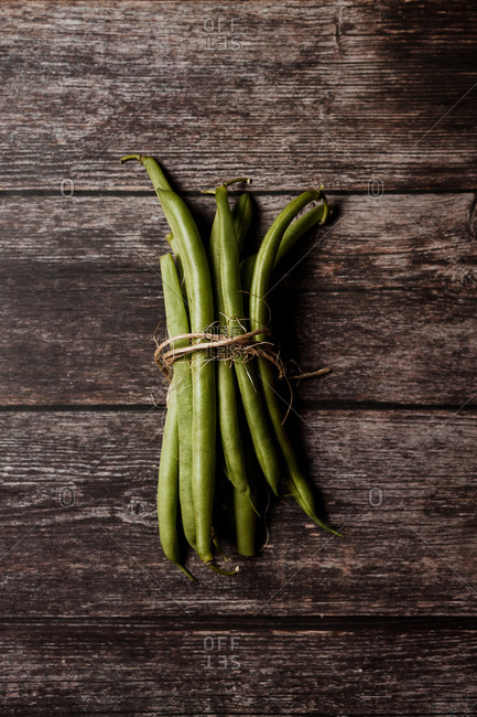 Top view of bundle of fresh green beans tied with rope on wooden rustic surface