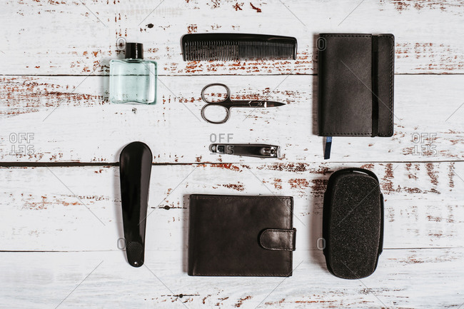 Overhead view of male manicure kit near bottle of perfume and leather purse on shabby surface