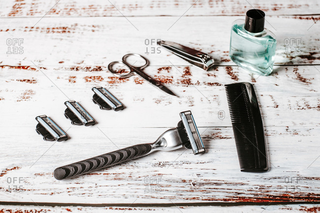 From above of sharp male razor near bottle of perfume and similar blades on rough surface