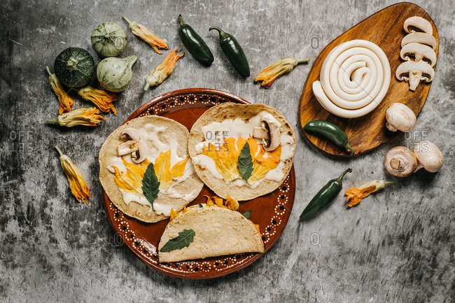 Top view of tasty tortillas with melted cheese and squash flowers near mushrooms and green chili peppers