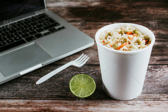 From above of plastic to go glass with delicious instant noodles near fork and lime on wooden table with laptop