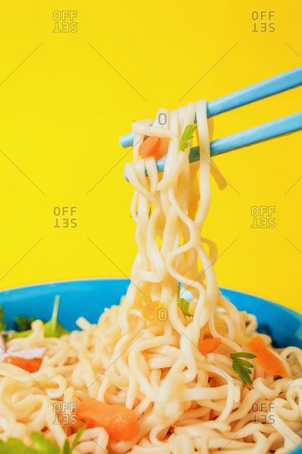 Tasty noodles from Japanese ramen soup with carrot and parsley on chopsticks on yellow background