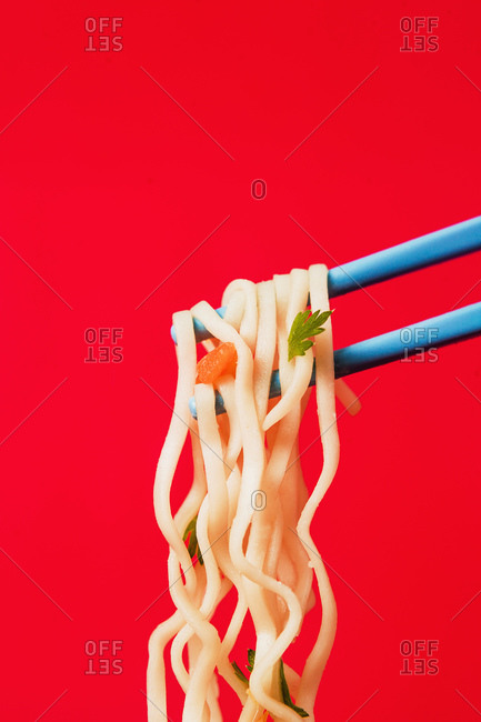 Tasty noodles from Japanese ramen soup with carrot and parsley on chopsticks on colorful background