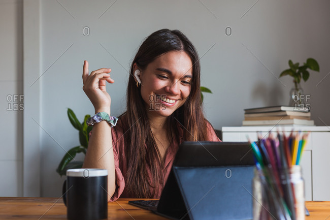 Happy young female in wireless earbuds and eyeglasses sitting at table with cup of hot drink and typing on modern netbook at home