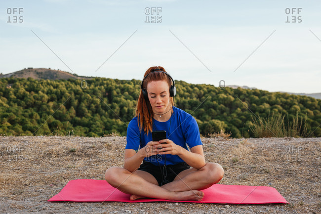 Serene female in sportswear sitting on mat and choosing songs from playlist while enjoying calm music in headphones after doing yoga in nature