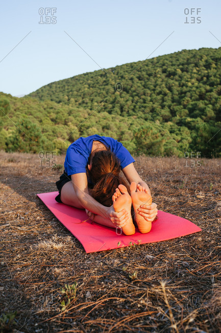 Anonymous flexible female sitting barefoot on mat at sunset and doing yoga in Pascimottanasana while practicing mindfulness