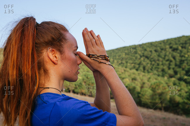 Headshot of tranquil female with Namaste hands with beads meditating with closed eyes at sunset in nature