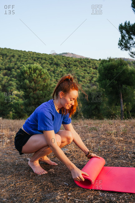 Side view of smiling barefoot female rolling up yoga mat after doing exercises in nature at sunset