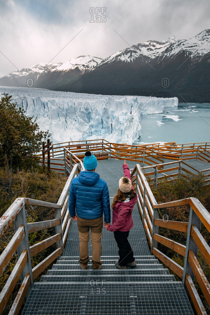 From above full body of cheerful couple in warm activewear climbing up stairway while exploring picturesque mountainous terrain with Perito Moreno glacier in Argentina
