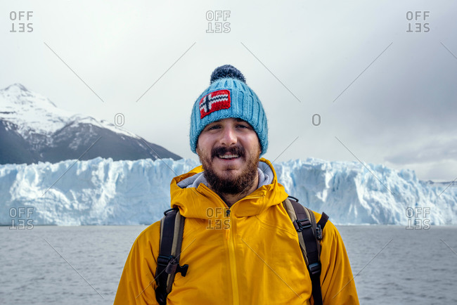 Cheerful adult bearded male tourist in warm clothes and hat with Norwegian flag looking at camera while standing against Perito Moreno glacier in Argentina