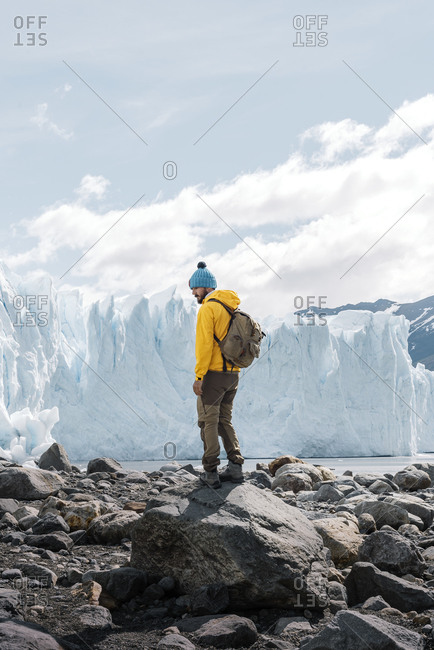 Back view of unrecognizable tourist in outerwear with backpack standing on stony terrain against gigantic blue ice formation while visiting Perito Moreno glacier in Argentina