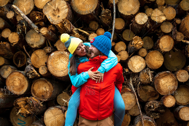 Happy young bearded man in warm clothes carrying cheerful girlfriend while spending time together in forest near pile of logs