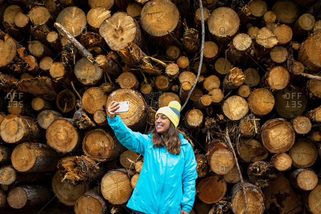 Happy young female tourist in warm clothes and hat smiling and taking selfie on mobile phone while standing near pile of cut logs in forest