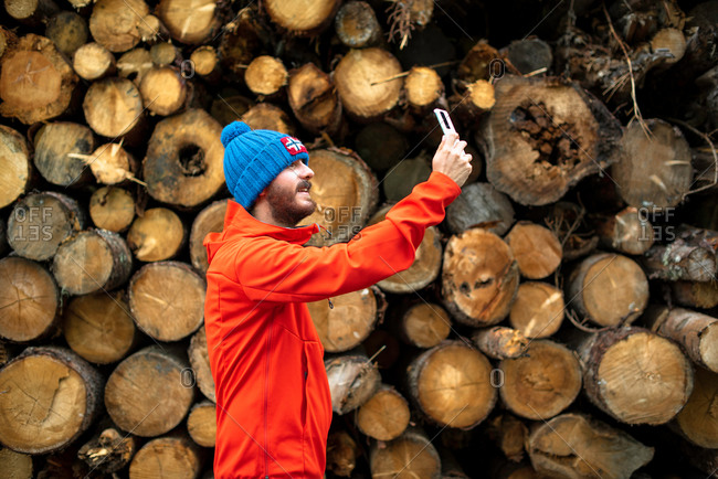 Happy young man tourist in warm clothes and hat smiling and taking selfie on mobile phone while standing near pile of cut logs in forest