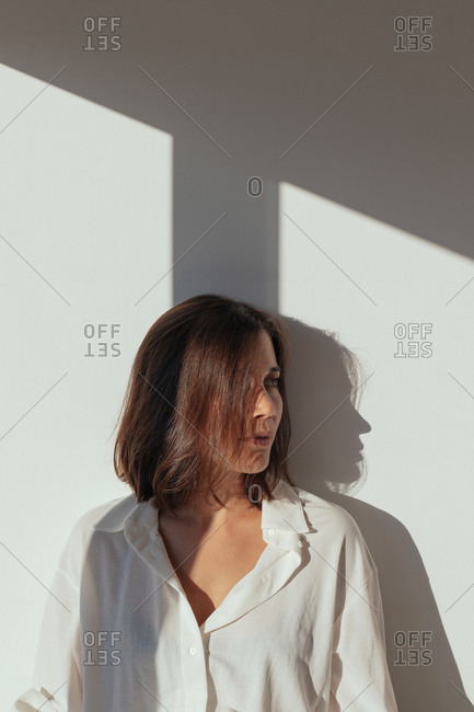 Sensual young female with brown hair in white shirt standing near wall and looking away in sunlight