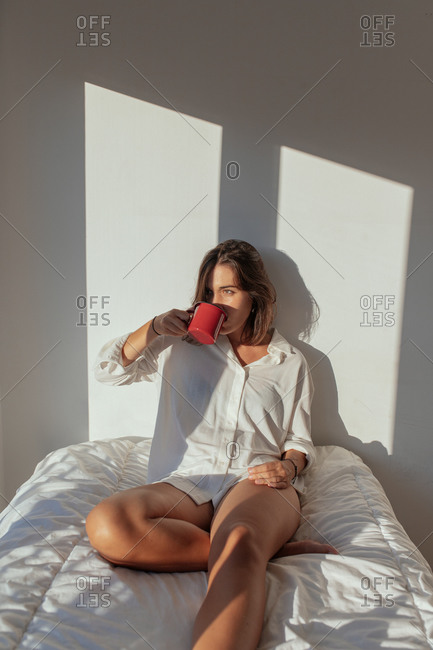 Happy young lady in white shirt sitting on comfortable bed and smiling while drinking cup of coffee in sunny morning looking away