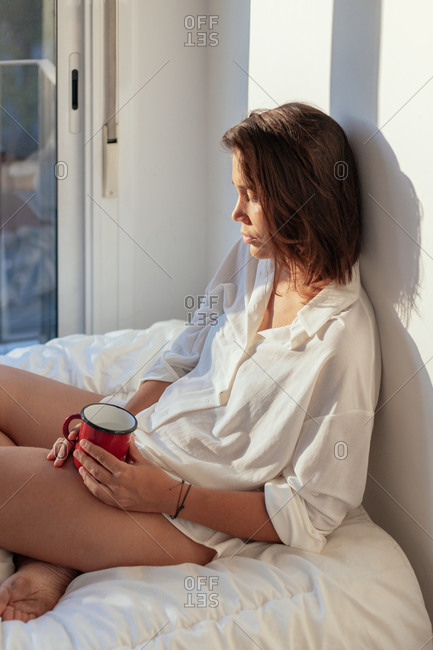 Side view of thoughtful young lady in white shirt sitting on comfortable bed and smiling while drinking cup of coffee in sunny morning looking away
