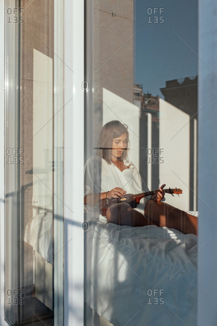 Alluring young female musician in white shirt sitting on comfortable bed and playing ukulele in sunny morning