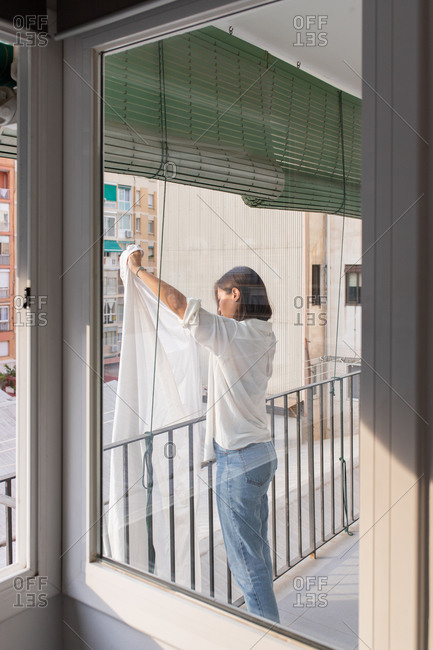Side view of young female in white shirt and jeans hanging laundry on clothesline on balcony