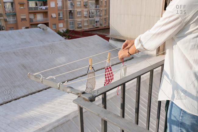 Cropped side view of unrecognizable young female hanging washed medical masks on clothesline on balcony