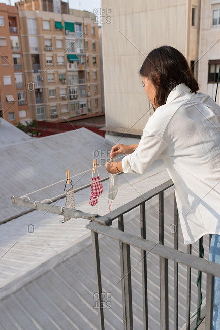 Side view of unrecognizable young female hanging washed medical masks on clothesline on balcony