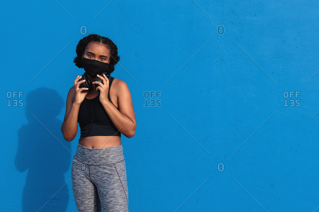 Young African American female athlete with headphones on neck in face mask and sportswear standing against blue background and looking at camera