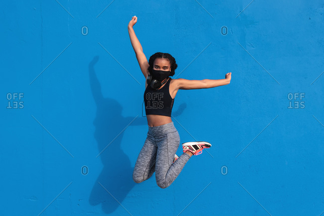 Full body of anonymous sporty young black lady in activewear and mask with headphones on neck jumping against blue wall