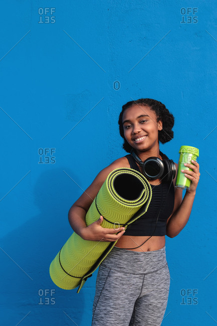 Cheerful young African American female athlete with headphones on neck in sportswear carrying rolled mat and thermos after workout on street against blue background