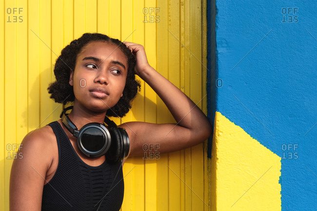 Young concentrated black female athlete in sportswear with headphones relaxing after training on street near colorful wall looking away