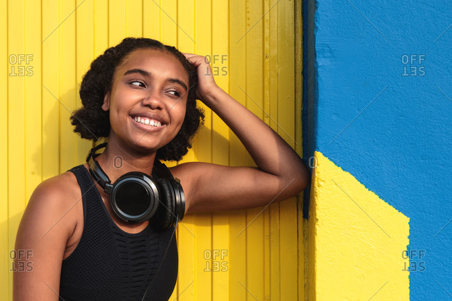 Young happy black female athlete in sportswear with headphones relaxing after training on street near colorful wall looking away