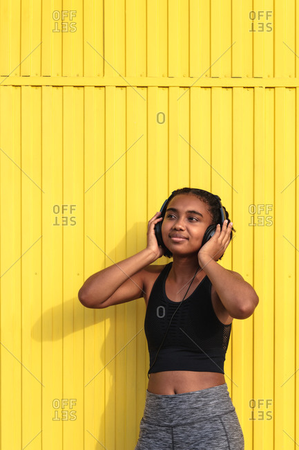 Side view of young happy black female athlete in sportswear with headphones relaxing after training on street near colorful wall looking away