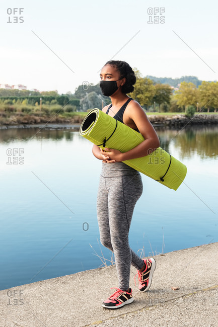 Full body side view of young African American lady in sportswear and mask walking in park near pond with rolled mat in hands before morning workout looking away