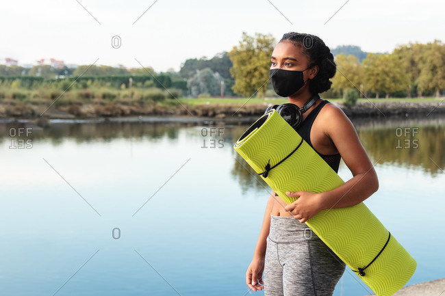 Side view of young African American lady in sportswear and mask walking in park near pond with rolled mat in hands before morning workout looking away