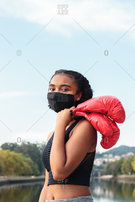 Serious young African American female boxer in protective mask and red gloves during workout on lake shore in park