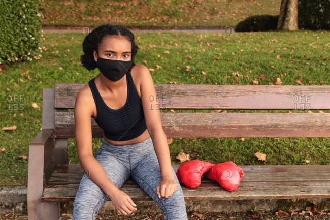 From above young black female athlete in protective mask and sportswear near red boxing gloves while sitting on bench in park before workout