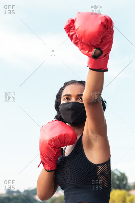Serious young African American female boxer in protective mask and red gloves punching during workout on lake shore in park