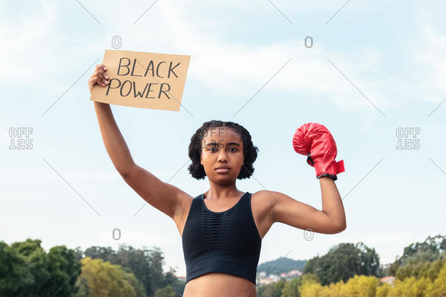 Determined young African American sportswoman in boxing gloves demonstrating placard with Black Power inscription after workout in park near lake