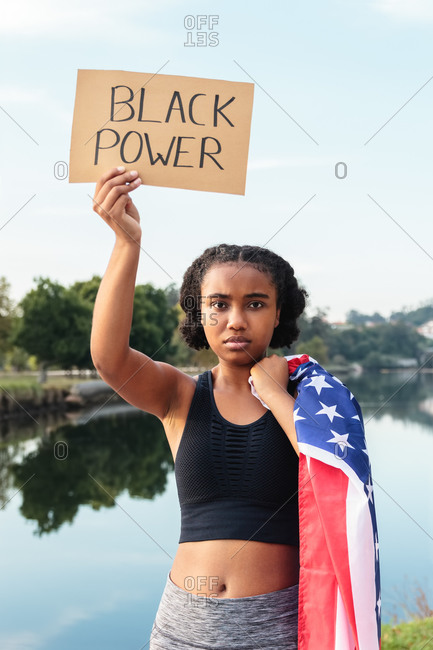 Focused African American female teenager in sportswear holding paper sheet with Black Power inscription and United States flag while standing near pond in park looking at camera