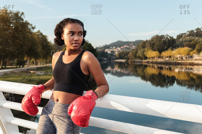 Contemplative young ethnic sportswoman in boxing gloves and sports clothes looking away while leaning on fence above river reflecting trees